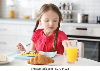 Cute little girl having breakfast at home