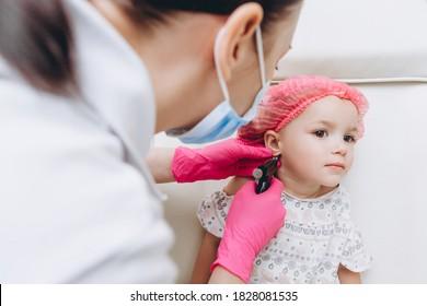 Cute little girl having ear piercing process with special piercing gun in beauty center by medical worker