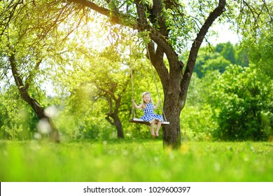 Cute little girl having fun on a playground outdoors in summer garden. Summer outdoor leisure for kids.