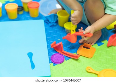 Cute little girl having fun playing colorful modeling clay, play dought at home, child care cooking food model, educational toys for kid creative for toddlers concept.