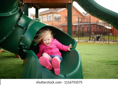 Cute little girl having fun on outdoor playground. Spring/summer/autumn active sport leisure for kids. Child on plastic slide