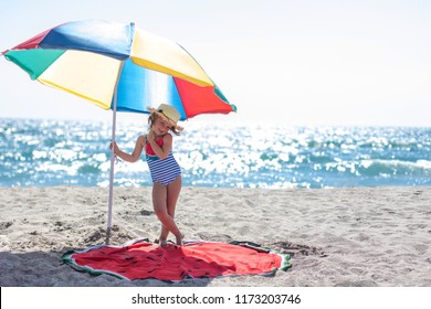 Cute little girl having fun at the beach on familly vacation. Familly, vacation, summer concept. Copy space to right.