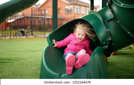 Cute little girl having fun on outdoor playground. Spring/summer/autumn active sport leisure for kids. Child on plastic slide