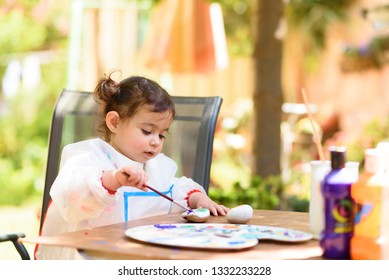 Cute little girl having fun, coloring with brush, writing and painting. Preschooler with paint at garden.Children paint. Kids drawing on a stone.  Preschoolers learn, doing homework. Creative toddler.