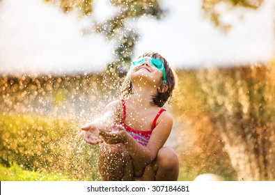 Cute little girl having fun outside in summer garden