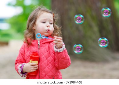 Cute little girl having fun with soap bubbles in summer park