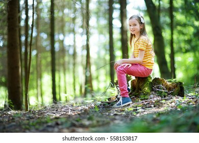 Cute little girl having fun during forest hike on beautiful summer day