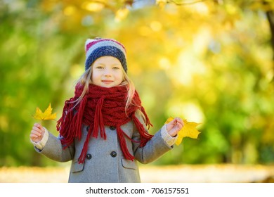 Cute little girl having fun on beautiful autumn day. Happy child playing in autumn park. Kid gathering yellow fall foliage. Autumn activities for children.