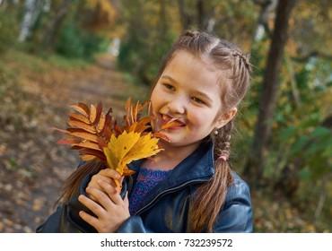 Cute little girl having fun on beautiful autumn day.