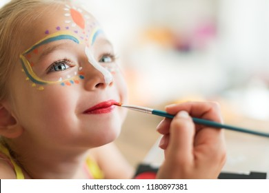Cute little girl having her face painted for Halloween party. Halloween or carnival family lifestyle background. Face painting, headshot close up.