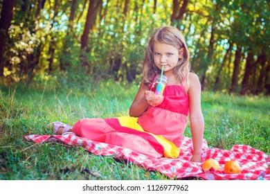 Cute little girl having some lemonade on a hot summer day