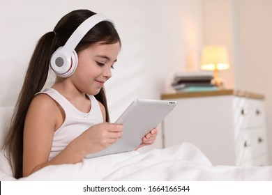 Cute little girl with headphones and tablet listening to audiobook in bed at home