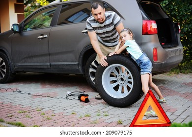 Cute little girl helps her father to change wheel on their family car on warm day in the yard