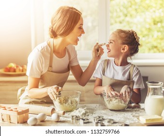 Cute Little Girl and Her Beautiful Mom in Aprons Playing. Happy daughter with Her Mother Laughing While Kneading the Dough in Modern Kitchen at Sweet Home. Smiling Family Cooking Tasty Biscuit.