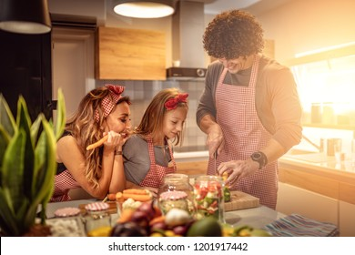 Cute little girl and her beautiful parents are cutting vegetables and smiling while making pickle in kitchen at home