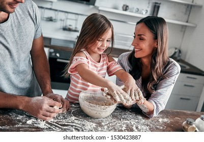 Cute little girl and her beautiful parents are knead flour fun for baking and smile while cooking in the kitchen and watching at the sticky dough in the hands.