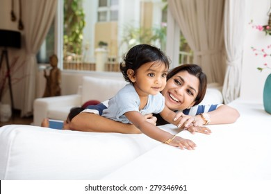 Cute little girl and her beautiful mother playing at home