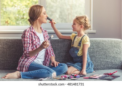 Cute little girl and her beautiful mother are doing makeup and smiling while sitting on couch at home