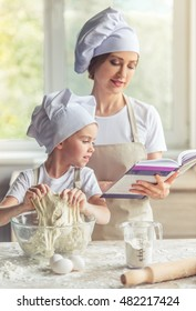 Cute little girl and her beautiful mom in aprons and cooking hats are reading recipe and smiling while kneading the dough in the kitchen