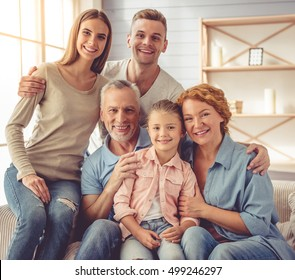 Cute little girl, her beautiful parents and grandparents are hugging, looking at camera and smiling while sitting on sofa at home