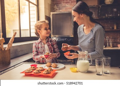 Cute little girl and her beautiful mother are talking and smiling while putting muffins on the plate