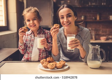 Cute little girl and her beautiful mother are looking at camera and smiling while drinking milk and eating muffins