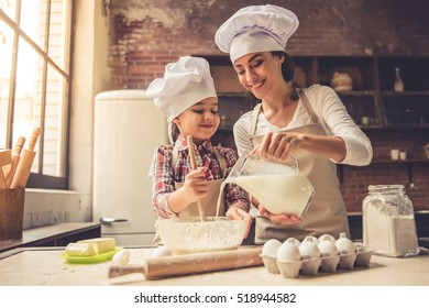 Cute little girl and her beautiful mother in chef hats are mixing muffin batter in the bowl and smiling while preparing it for baking. Mother pouring milk