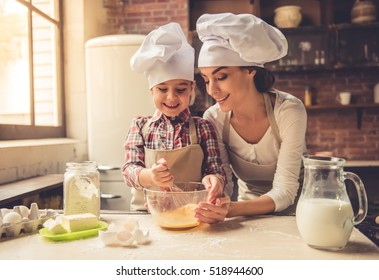 Cute little girl and her beautiful mother in chef hats are whisking eggs and smiling while baking at home