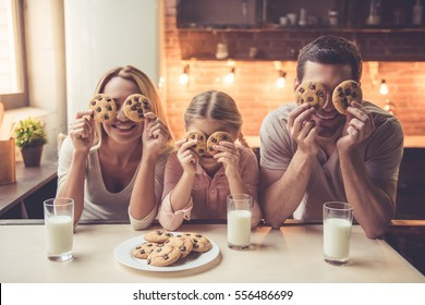 Cute little girl and her beautiful parents are having cookie with milk and smiling while standing in kitchen at home