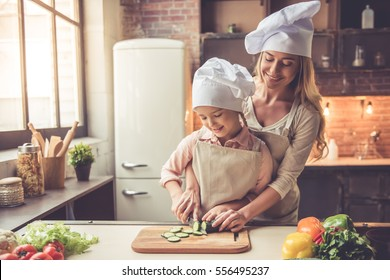 Cute little girl and her beautiful mom in chef's hats are cutting vegetables and smiling while cooking in kitchen at home
