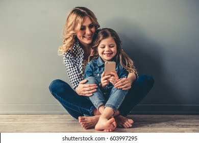 Cute little girl and her beautiful young mom are sitting together on the floor, using a smart phone and smiling, on gray background
