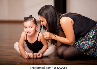 Cute little girl and her dance instructor smiling and having fun during class