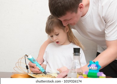 Cute little girl with her father draw different things by 3d pen with a gold plastic handle. Mathematics. Engineering. Technology. Robotics. STEM education.