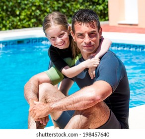 c6baa90d2f cute little girl with her father in a wetsuit near the pool in the summer