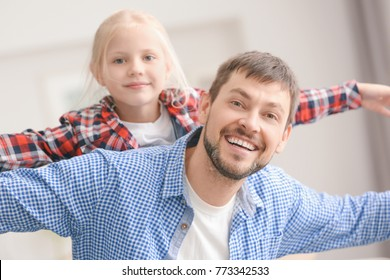 Cute little girl with her father playing at home