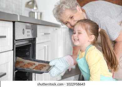Cute little girl and her grandmother taking out cookies from oven on kitchen