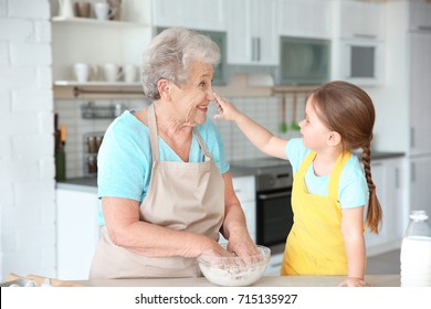 Cute little girl and her grandmother cooking on kitchen
