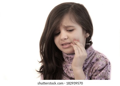 Cute little girl with her hand held to her face with painful expression showing toothache