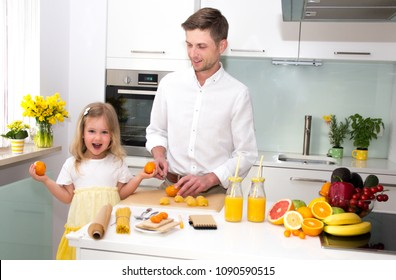 Cute little girl and her handsome father are cutting vegetables and smiling while cooking in kitchen at home.