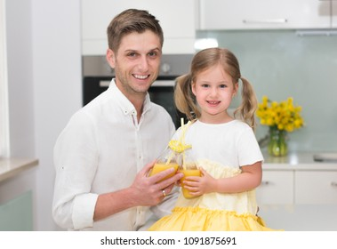 Cute little girl and her handsome father are drinking juice and smiling while cooking in the kitchen at home.
