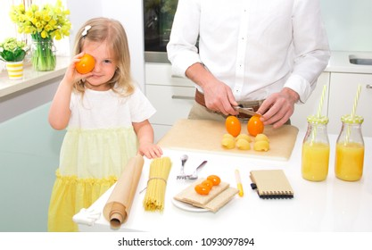 Cute little girl and her handsome father cooking and smiling in the kitchen at home.