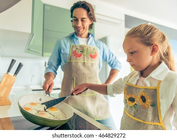 Cute little girl and her handsome father in aprons are cooking fried eggs in kitchen at home