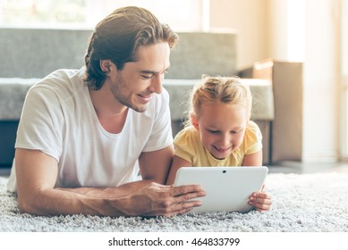 Cute little girl and her handsome father are using a digital tablet and smiling while lying on the floor at home