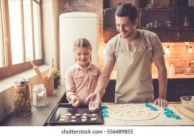Cute little girl and her handsome dad are using cookie cutters and smiling while baking in kitchen at home