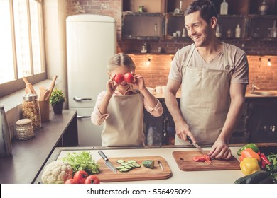 Cute little girl and her handsome dad are having fun while cooking in kitchen at home