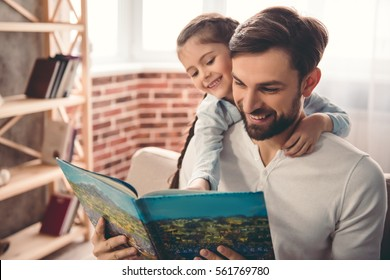 Cute little girl and her handsome father are reading a book and smiling while sitting on couch at home