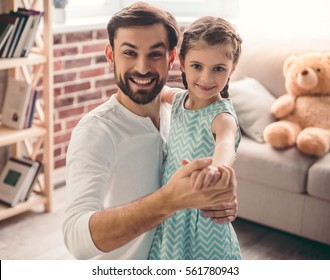 Cute little girl and her handsome father are looking at camera and smiling while dancing together at home