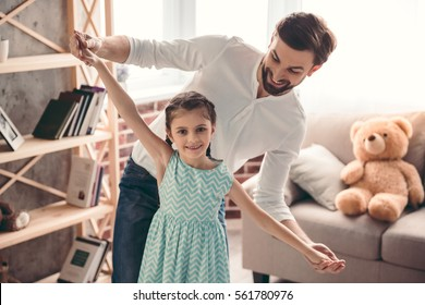 Cute little girl and her handsome father are smiling while dancing together at home