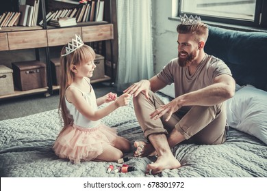 Cute little girl and her handsome bearded dad in crowns are smiling while playing in her room. Girl is painting her dad nails