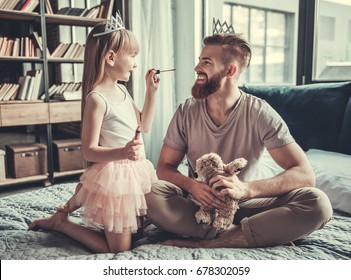 Cute little girl and her handsome bearded dad in crowns are smiling while playing in her room. Girl is doing her dad makeup